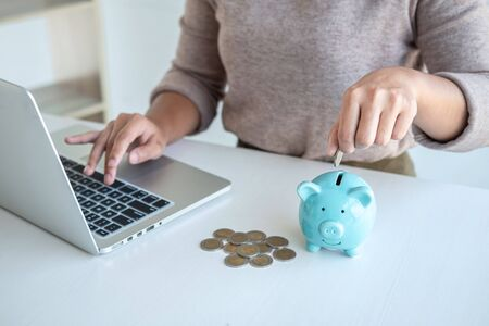 Young woman putting coins into piggy bank planning growing saving to strategy with money box for future plan fund of travel, education, home and retirement. Standard-Bild