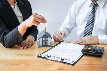 Home Insurance and Real estate investment concept, Sale agent giving house key to new client after signing agreement contract with approved property application form.