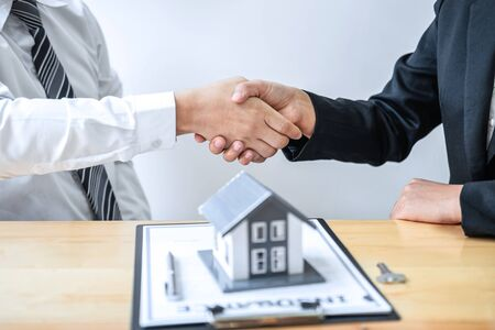 Real estate agent are shaking hands after good deal and giving house, keys to customer after discussing and signing contract to buy house with approved application form.