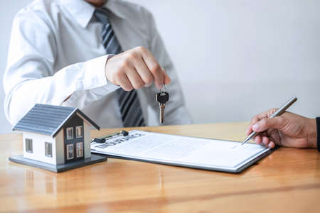 Home Insurance and Real estate investment concept, Sale agent giving house key to new client after signing agreement contract with approved property application form. Banque d'images
