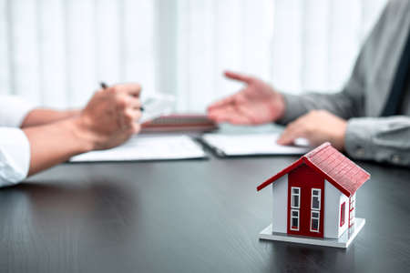 Estate agent are presenting home loan to client and discussing to decision signing agreement contract form, Home Insurance and Real estate investment concept. Stock Photo