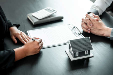 Real estate agent working sign agreement document contract for home loan insurance approving purchases for client with house model and key on table.