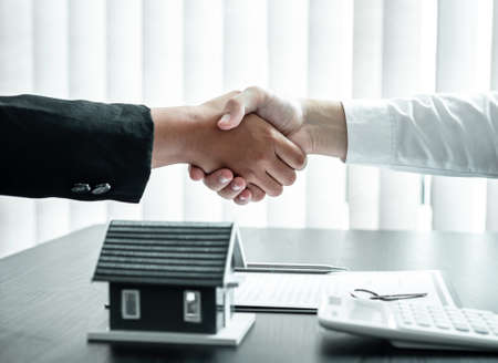Estate agent and client are shaking hands after good deal home loan after discussing and signing contract to rent a house with approved insurance form. Imagens