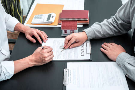 Real estate agent are presenting home loan and giving keys to customer after signing contract to rental house with approved property application insurance form contract.