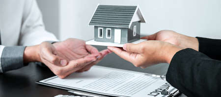 Sale Estate agent giving house model to new client after signing agreement contract with approved property form, Home Insurance and Real estate investment concept.