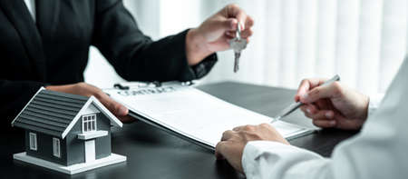 Estate agent are presenting home loan and sending keys to client after signing contract to rental house Insurance with approved property form. Imagens