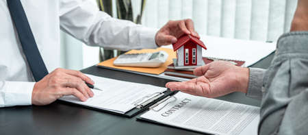 Estate agent are presenting home loan to client and discussing to decision signing agreement contract form, Home Insurance and Real estate investment concept.