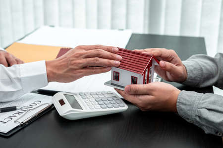 Estate agent are presenting home loan to client and discussing to decision signing agreement contract form, Home Insurance and Real estate investment concept. Imagens