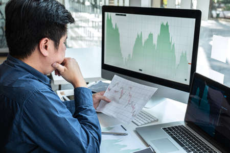 Businessman investor working in traders marketing and planning and analyzing pointing on the stock chart data presented and deal on a stock exchange to business profit.