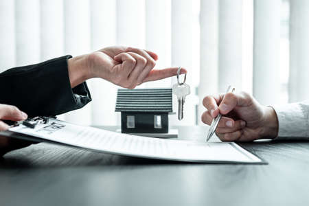 Estate agent are presenting home loan and sending keys to client after signing contract to rental house Insurance with approved property form. Standard-Bild