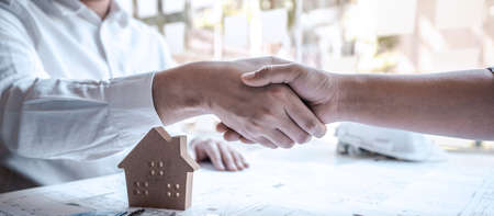 Team of architects or engineering shaking hands while working cooperation on engineer tools and construction drawings inspection, discussing planning architectural project on blueprint, model house.