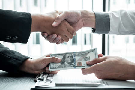 Business people shaking hands with money in hands from their partner to give success the deal contract in a corruption scam, illegal and dishonest.