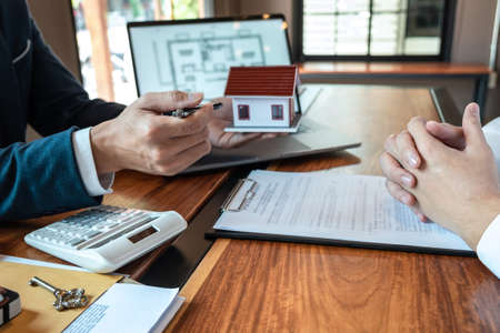 Sale purchase contract to buy a house, Real estate agent are presenting home loan and giving keys to customer after signing contract to buy house with approved property application form. Standard-Bild