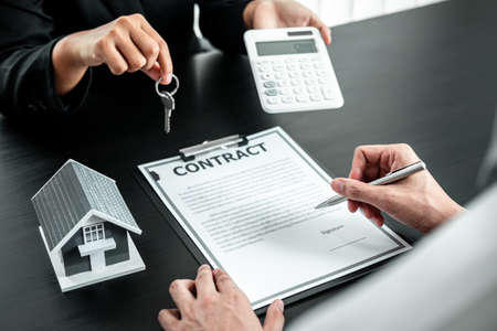 Estate agent are presenting home loan and sending keys to client after signing contract to rental house Insurance with approved property form.