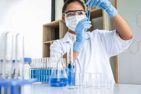 Female scientific researcher or doctor working in laboratory about virus and vaccine antiretroviral coronavirus covid19 researcher investigations with test tubes flask and blue liquid solution.