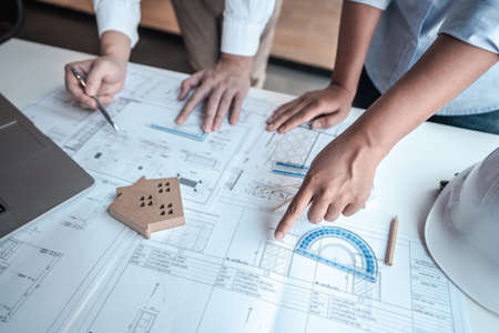 Architects or engineering team consulting and analyzing working on objects tools and construction drawings inspection planning new architectural project on blueprint and model house in modern office.