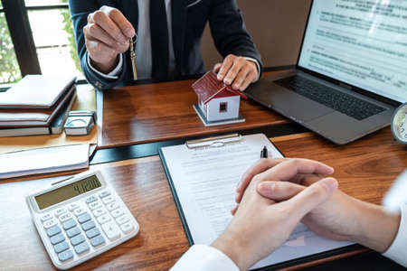 Real estate agent are presenting home loan and sending keys to customer after signing contract to buy house with approved property application form, Insurance Home concept. Standard-Bild