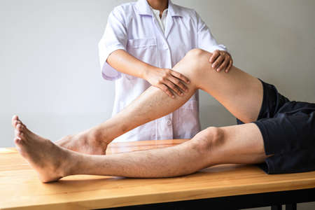 Doctor or Physiotherapist working examining treating injured leg of athlete male patient, Doing the Rehabilitation therapy pain in clinic. Standard-Bild