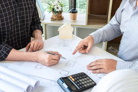 Team of architects or engineering consulting and analyzing working on objects tools and construction drawings inspection, discussing planning new architectural project on blueprint and model house.