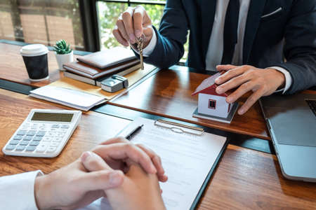 Sale purchase contract to buy a house, Customer sending money buying home loan and giving keys from Agent after signing contract to buy house with approved form, Insurance and Home concept.