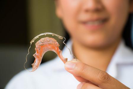 Dentist holding retainer
