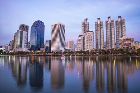 Modern night city skyline with lights reflection at Benjakitti Park in Bangkok Thailand Stock Photo