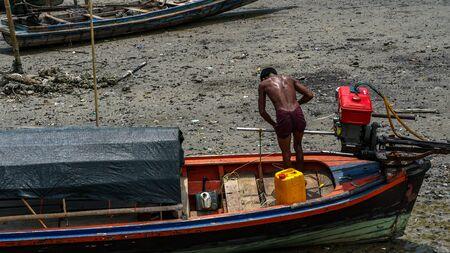 Moken man is repairing boat engines in Moken Village Thailand Redactioneel