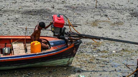 Moken man is repairing boat engines in Moken Village Thailand Stockfoto - 137009344
