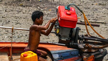 Moken man is repairing boat engines in Moken Village Thailand Stockfoto - 137009345