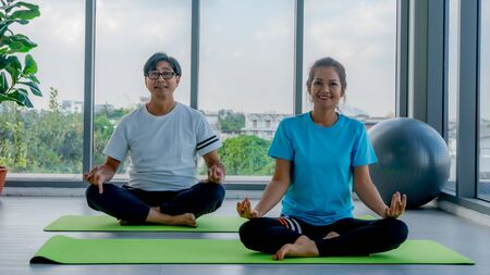 Old man and woman playing yoga