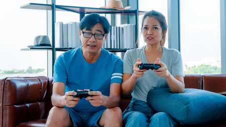Old man and woman playing video game