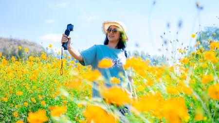 Beautiful women blogging in the flowers garden Stockfoto