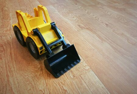Group of yellow construction truck toys on wooden floor and background.