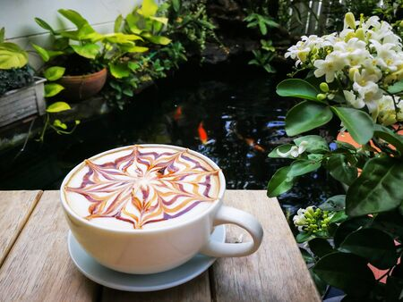 homemade latte art coffee with chocolate sauce and caramel sauce  on Milk foam on wooden table beside the fish pond. Fancy carp in the pond