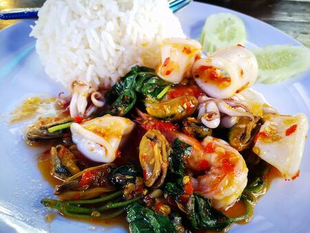 Stir Fried Basil with Seafood on white dish. Key ingredient  squid, shrimp and Mussels.