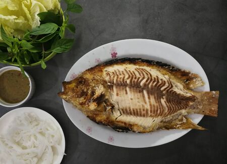 Salt-Burning Fish on white dish, healthy food and weight control. Food on marble surface. Stock Photo