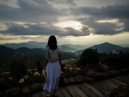 First light of day and the woman breathe fresh air , watching  sunshine and mist on top of the mountain.  Mountain with The fog faded. This place at KhaoKho, Petchabul, Thailand. Фото со стока