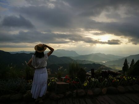 First light of day and the woman breathe fresh air , watching  sunshine and mist on top of the mountain.  Mountain with The fog faded. This place at KhaoKho, Petchabul, Thailand. Banco de Imagens