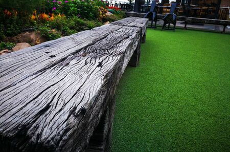 Long wooden chair made by log on artificial green grass.