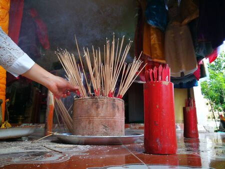 """Focusing on Red Esiimsi, piece of number for prediction, blurred focus on Incense burner and Carved candle at Goddess of Mercy at """"Chao Mea Ta Kein"""" Shrine, Pathumthani, Thailand."""