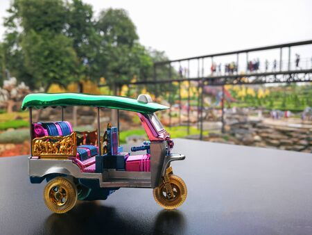 Souvenir mini tuk tuk on Black surface table or road and blur park for background. Thai traditional taxi in Bangkok Thailand. 免版税图像