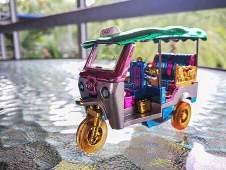 Souvenir mini tuk tuk on Black surface table or road and blur park for background. Thai traditional taxi in Bangkok Thailand.