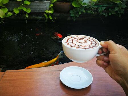 Human hand holding cup of  latte art coffee with chocolate sauce and caramel sauce  on Milk foam beside the fish pond.  写真素材