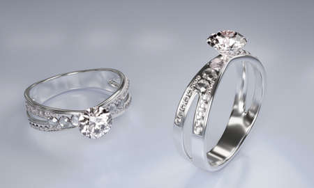 Diamond rings made of platinum gold decorated with many small diamonds placed on a white surface. 3D Rendering 版權商用圖片