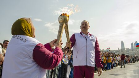 President of Azerbaijan Ilham Heydar oglu Aliyev passes the torch relay at the First European Olympic Games in Baku in 2015