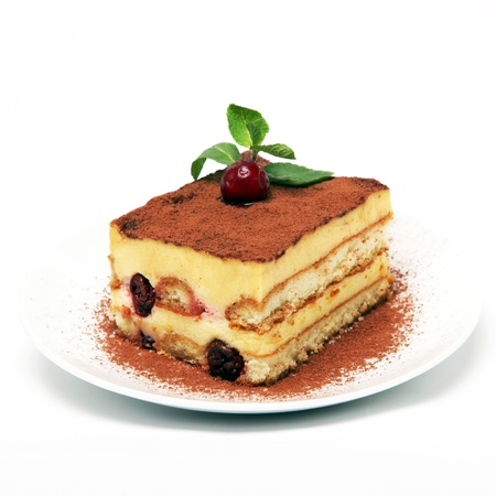 A piece of tiramisu cake with cherries on a white plate closeup