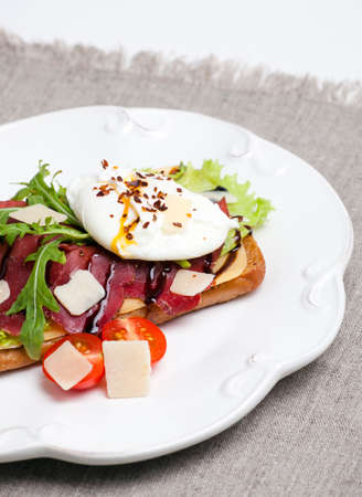 poached: Sandwich with poached eggs on a white plate Stock Photo