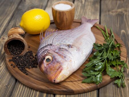 major ocean: Fresh fish Pagr on a wooden board with lemon and spices