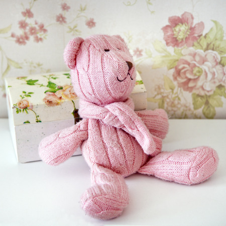 pink teddy bear: gift pink teddy bear knitted sits on a shelf