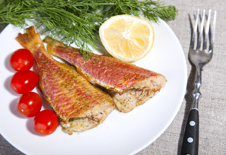 mullet: grilled Mediterranean red mullet fish on a plate with herbs and lemon Stock Photo